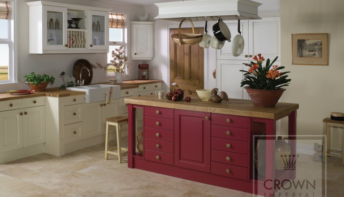 Interior image of kitchen with red painted island and oyster painted cabinetry