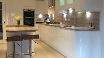 Image of renovated kitchen with white cabinets, wood and grey accents