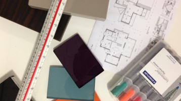 Image of design tools; blueprints, centering ruler, glass samples and markers